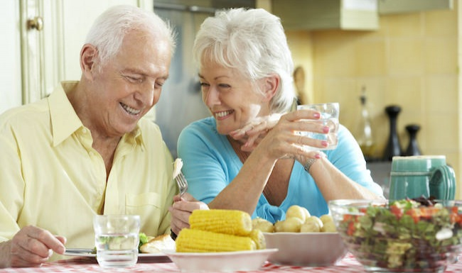 Older couple eating vegetables in a bright room